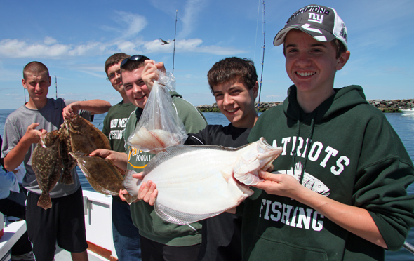 Members of the Ward Melville High School Fishing Club show off some fluke caught aboard the Port Jefferson open boat Celtic Quest.