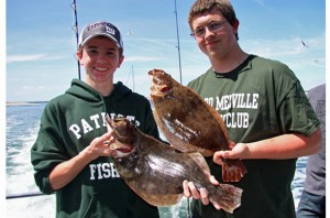 Members of the Ward Melville High School Fishing Club show off a pair of keepers that fell to bucktail and teaser rigs.